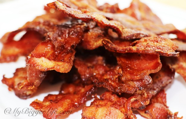 Crispy, crunchy bacon stacked high on a white plate