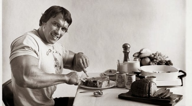 Arnold Schwarzenegger eating a meal at the table - How Important Is Protein To My Diet?