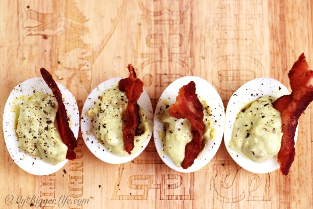 Avocado deviled eggs topped with bacon on wooden cutting board