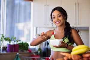 Woman eating healthy in kitchen